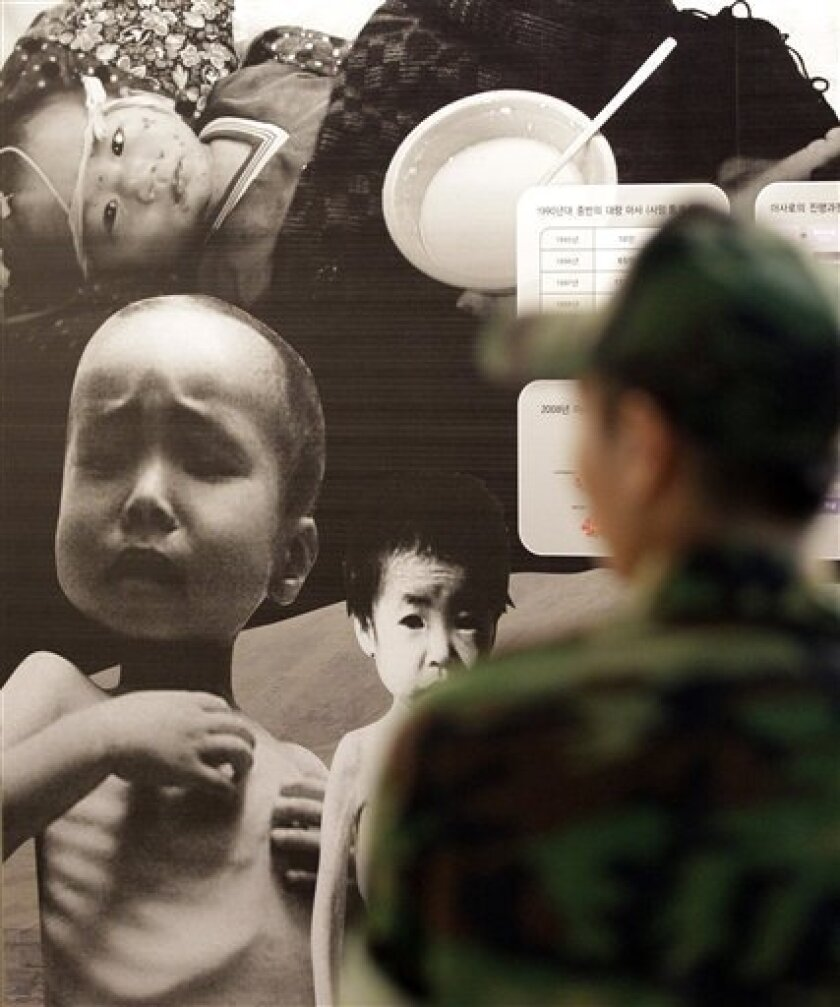 A South Korean soldier walks by a huge poster depicting North Korea's food crisis at the Korea War Memorial Museum in Seoul, South Korea, Tuesday, Sept. 7, 2010. North Korea requested a shipment of rice, cement and heavy equipment days after South Korea offered relief aid to its communist neighbor to help it recover from recent flooding, the Unification Ministry said Tuesday. (AP Photo/ Lee Jin-man)