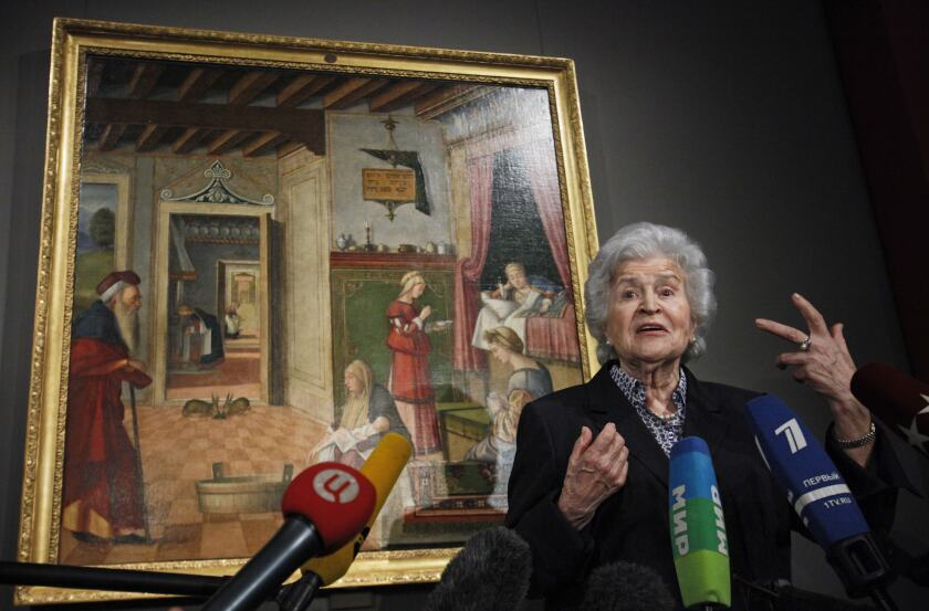 FILE - In this Friday, April 27, 2012 file photo, Irina Antonova, Director of the Pushkin Fine Arts Museum, speaks in front of a masterpiece by Vittore Carpaccio at a news conference on celebrations marking the museum's 100th anniversary in Moscow, Russia. Antonova, a charismatic art historian who presided over one of Russia's top art museums for more than half-a-century, has died in Moscow on Monday, Nov. 30, 2020. She was 98. The Pushkin State Museum of Fine Arts said that Antonova last week tested positive for the coronavirus, which exacerbated her longtime chronic heart ailments.(AP Photo/Alexander Zemlianichenko, File)