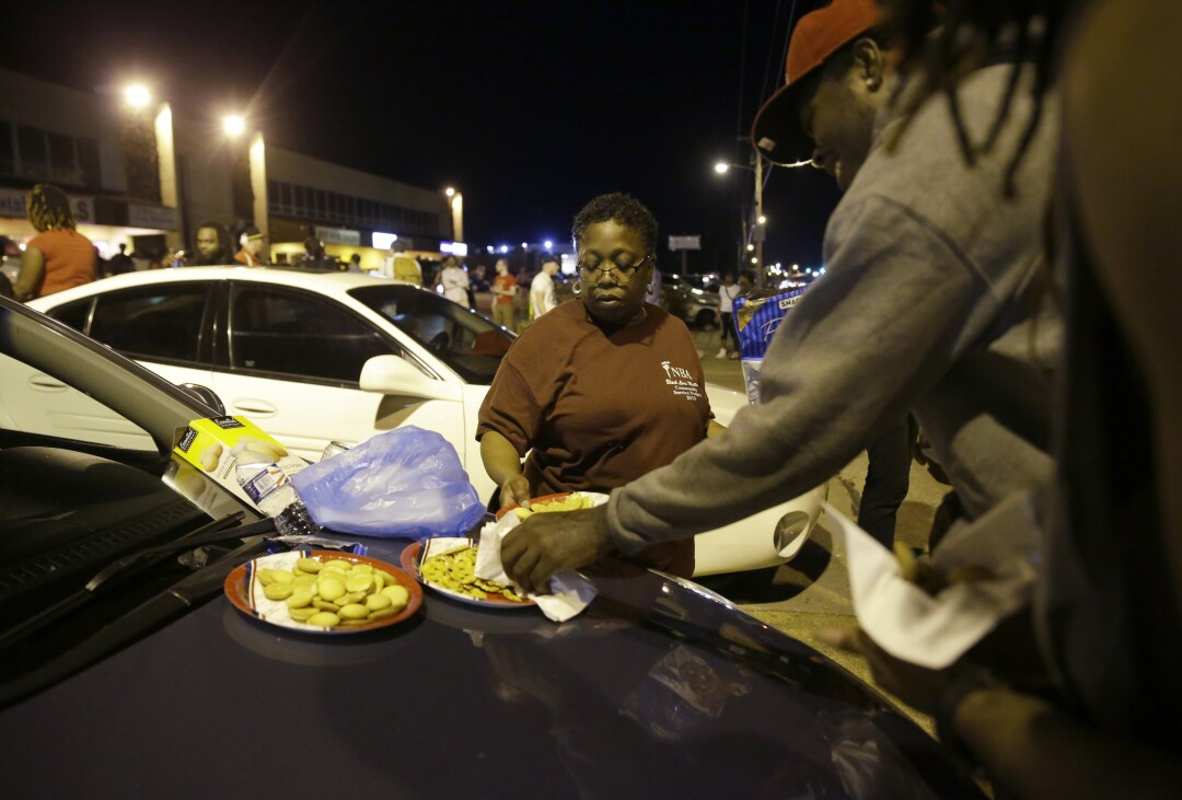 """Momma Cat"" Daniels puts out snacks as protesters gather along West Florissant Avenue in Ferguson, Mo., Tuesday night."
