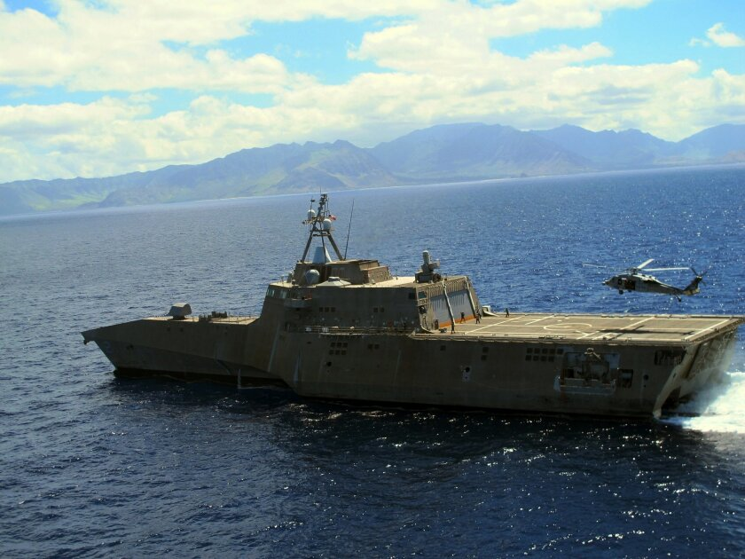 """A Navy helicopter lands on the USS Independence in waters off Honolulu on Thursday, July 24, 2014. Navy Secretary Ray Mabus says operating costs for the service's newest ships, littoral combat ships like the Independence,  will decline and """"become more normal"""" over time. (AP Photo)"""