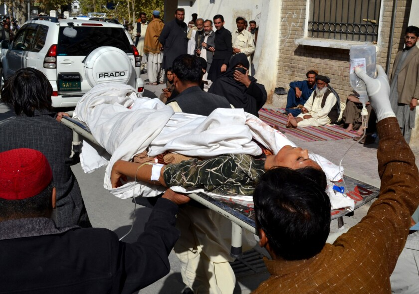 Volunteers carry an injured polio-vaccination worker to a hospital in Quetta, Pakistan, on Nov. 26 after gunmen attacked a vaccination team, killing four.