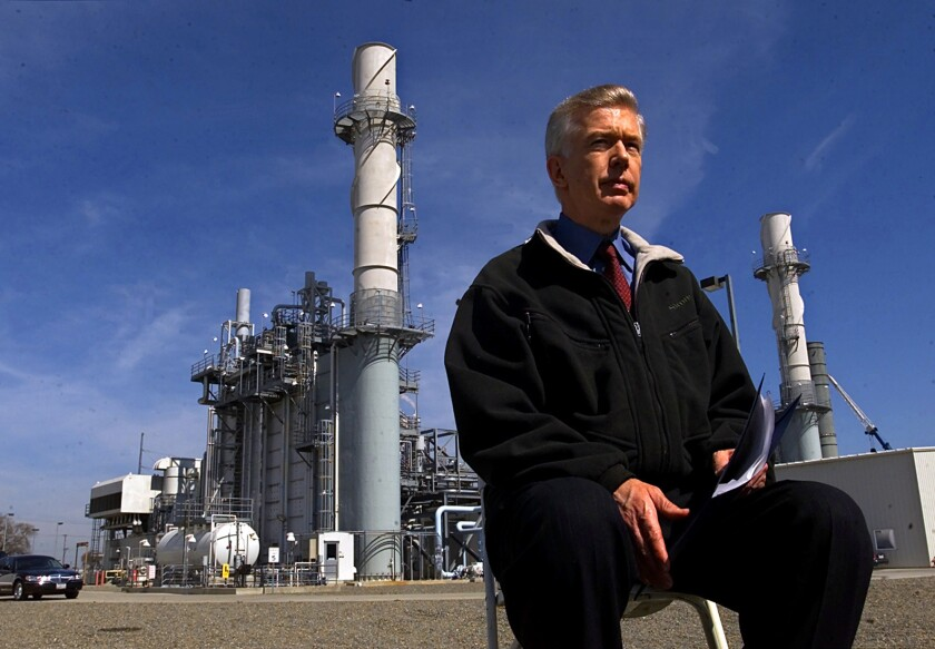 A man sits in a chair outside at a power plant.