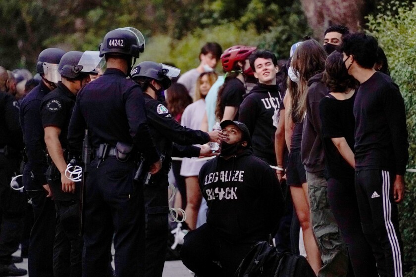 People wait to be processed by law enforcement officers on a Wilshire Boulevard sidewalk Monday in Westwood.