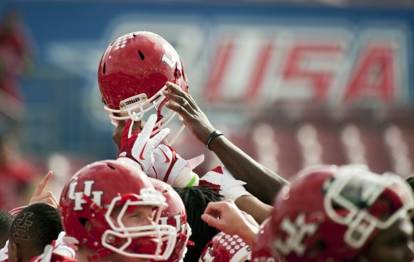 FILE - In this Dec. 3, 2011, file photo, Houston players gather before a Conference USA championship NCAA college football game against Southern Mississippi in Houston. Conference USA announced Wednesday, May 25, 2016, that it has reached a multiyear agreement to have its football and basketball games and other sports televised by four networks, CBS Sports Network and American Sports Network, beIN Sports, and ESPN. (AP Photo/Dave Einsel, File)