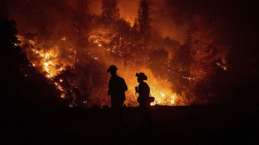 Firefighters monitor a backfire while battling the Ranch Fire, part of the Mendocino Complex Fire, o