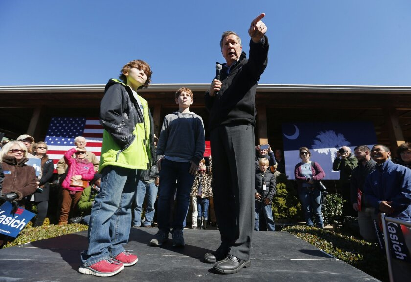 Republican presidential candidate, Ohio Gov. John Kasich speaks with children during a campaign stop, Saturday, Feb. 13, 2016, in Mauldin, S.C. (AP Photo/Paul Sancya)