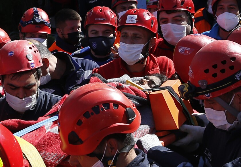 Medics and rescue personnel carry into an ambulance an injured person from the debris of a collapsed building in Izmir, Turkey, Saturday, Oct. 31, 2020. Rescue teams on Saturday ploughed through concrete blocs and debris of eight collapsed buildings in Turkey's third largest city in search of survivors of a powerful earthquake that struck Turkey's Aegean coast and north of the Greek island of Samos, killing dozens of people. Hundreds of others were injured. (AP Photo/Emrah Gurel)