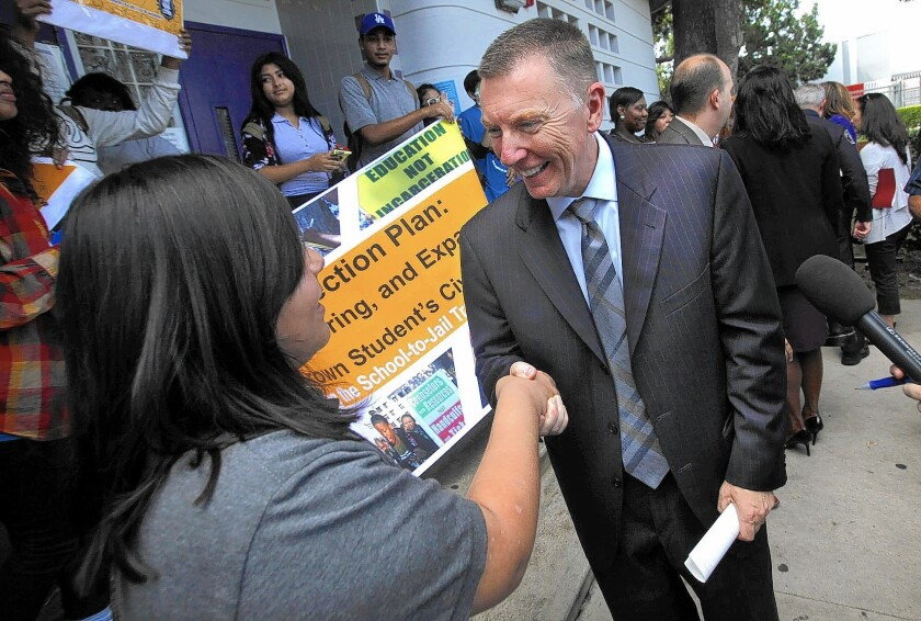 L.A. schools Supt. John Deasy shakes hands with Manual Arts High School senior Laura Aguilar, 17. The school board is scheduled to meet behind closed doors Tuesday to plan Deasy's Oct. 21 job evaluation. His supporters are concerned that he won't remain in the job until then.