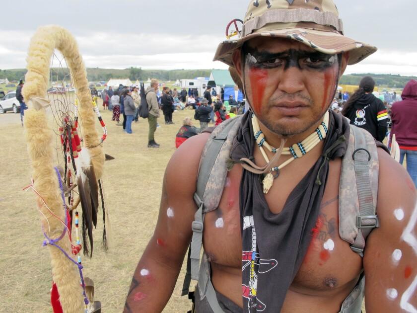 """Jon Don Ilone Reed, veterano del ejército y miembro de la tribu sioux río Cheyenne en South Dakota, posa para una fotografía en una manifestación contra la construcción de un oleoducto cerca de la reservación sioux Standing Rock en el sur de North Dakota, el jueves 25 de agosto de 2016. Reed dijo que peleó en Irak y ahora lucha """"por nuestros niños y nuestra agua"""". (AP Foto/James MacPherson)"""