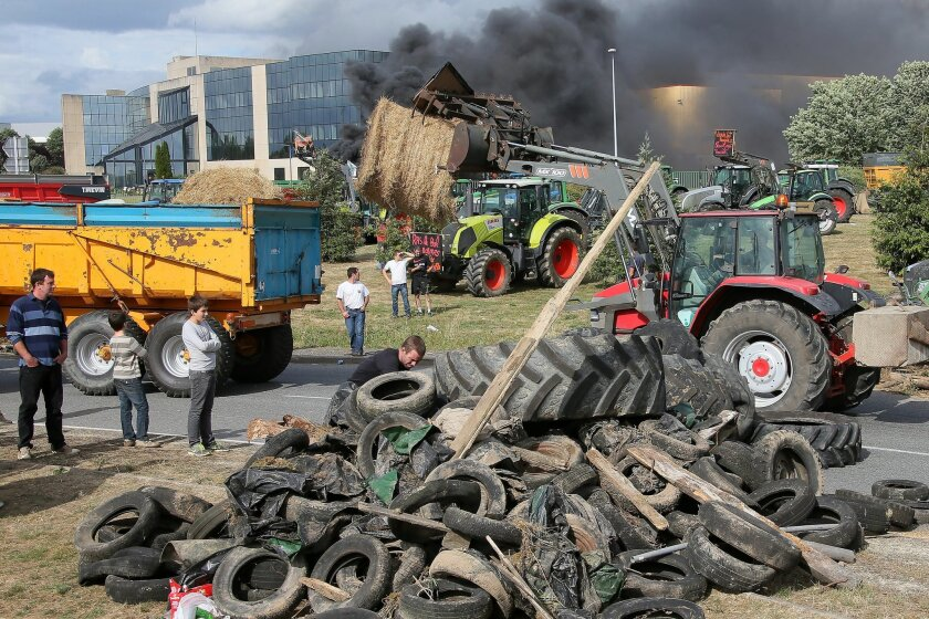 French farmers gather in front of Lactalis' factory, Monday, July 27, 2015, in Laval, western France in order to protest against importation of foreign meat and milk products in France. The protests are a rejection of the government offer to back loans to the farmers and delay tax payments as part of a 600 million euro plan. (AP Photo/David Vincent)