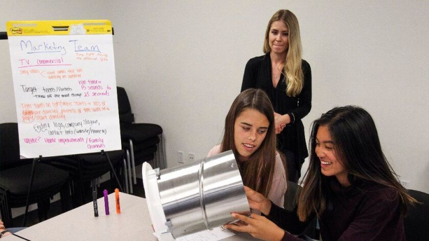 """Roosevelt Middle School students Julia O'Neill, seated left, and Caitlyn Cielo, both 14, look at a Solatube as Marketing Specialist Rachel Ochinero oversees students in the """"Talent Cities"""" program."""