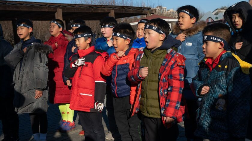 Boys pledge and chant before stripping to the waist for a run through a freezing Beijing park.