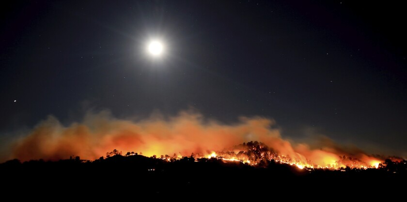 A wildfire burns under the waning moon early Sunday morning, June 7, 2020, near Winters, Calif. (Kent Porter/The Press Democrat via AP)