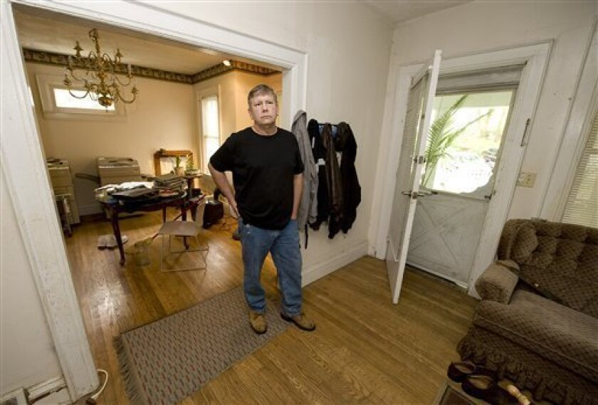 In this photo made Friday, June 5, 2009, Jerry Turner stands in the living room of the Charleston W.Va. home his mortgage servicer, Select Portfolio, collected payments on for six years before he found out that it had been foreclosed on and later auctioned off. Turner still lives at the home while his case against Select Portfolio is pending in West Virginia state court. (AP Photo/Bob Bird)