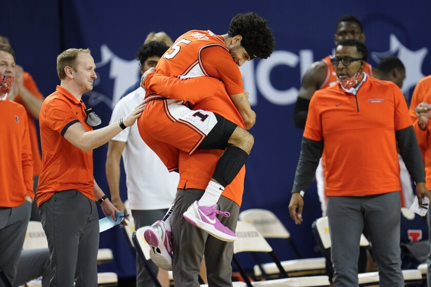 Illinois guard Andre Curbelo (5) jumps into the arms of head coach Brad Underwood in the second half of an NCAA college basketball game against Michigan in Ann Arbor, Mich., Tuesday, March 2, 2021. Illinois won 76-53. (AP Photo/Paul Sancya)