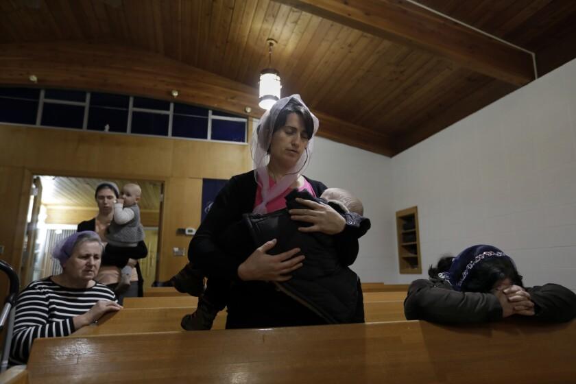 Yuliia Kulybchuk, 33, holds her son Tymofii, 20 months, during worship at Calvary Free Lutheran Church in Bismarck.