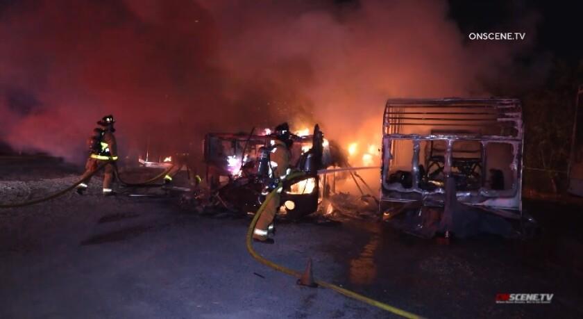 Chula Vista firefighters work to extinguish a blaze that destroyed three RVs Monday night at the San Diego Metro KOA Resort.