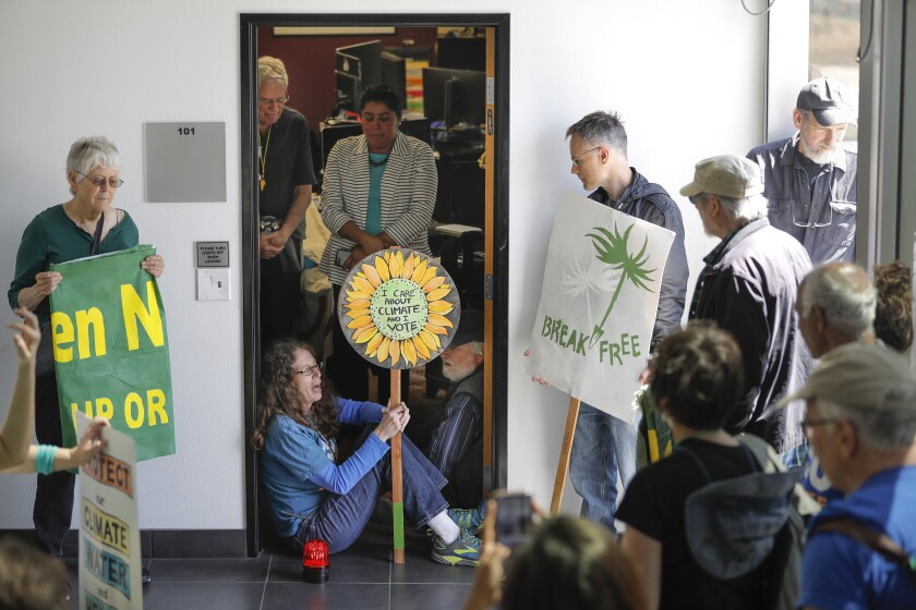 SAN DIEGO, CA 3/19/2019: Masada Disenhouse of La Mesa, the co-founder of San Diego350 sits in the doorway of Rep. Susan Davis' San Diego office on Adams Avenue. She and other demonstrators have held protests at the offices of local members of Congress demanding support for the Green New Deal.