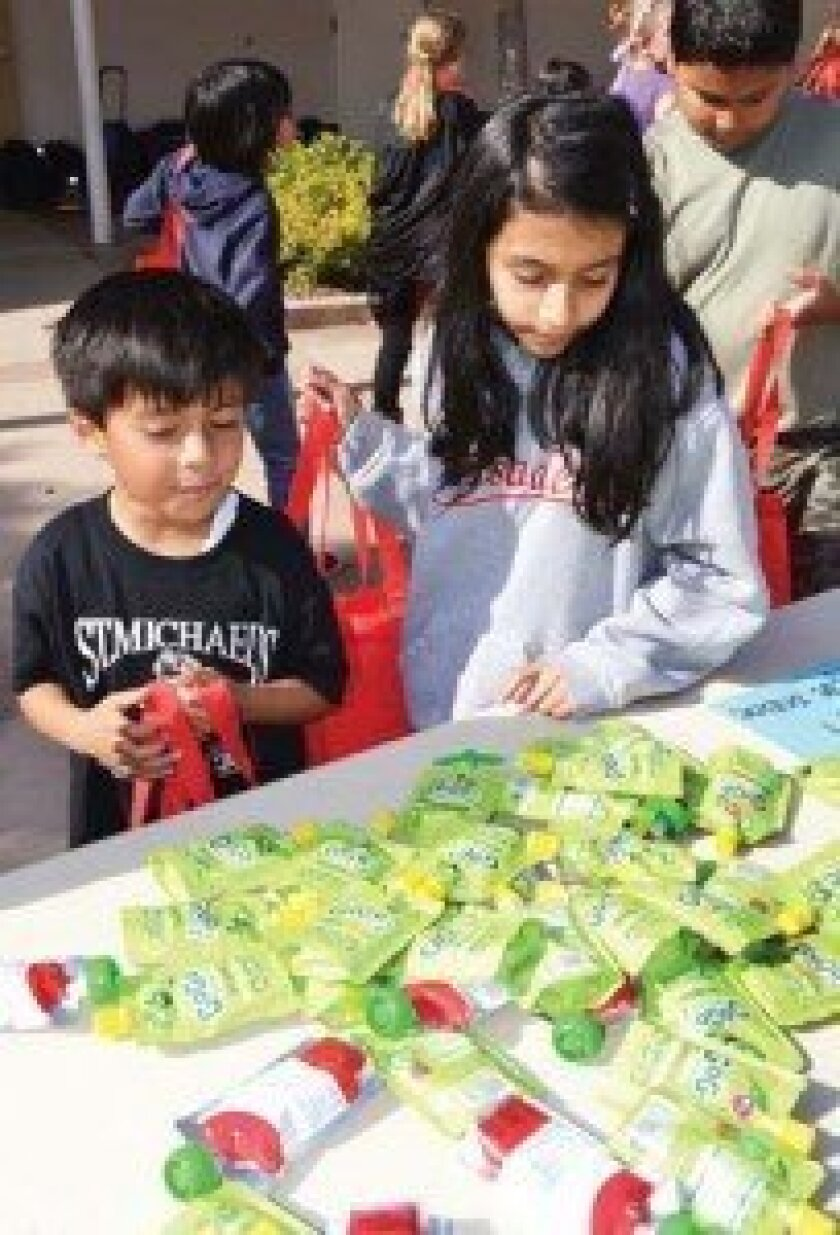 St. Michael's kindergartner Lorenzo Jaramillo and fourth-grader Amelia Dias selecting an apple sauce pouch for their bag that they are to give to a homeless person they encounter. Photo by Elizabeth Marie Himchak