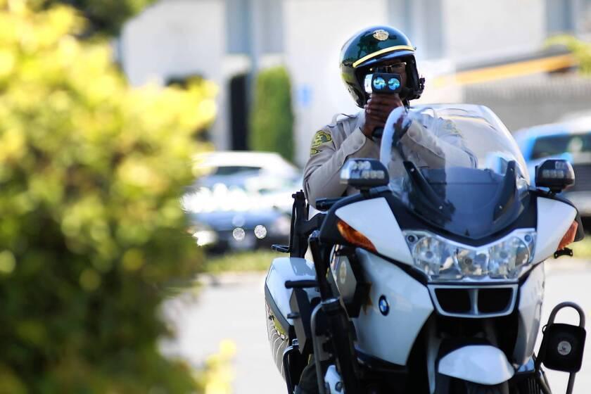 Los Angeles County Sheriff's Deputy Elton Simmons checks a motorist's speed in La Mirada.