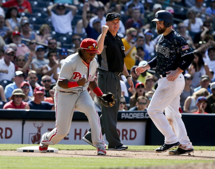 Philadelphia Phillies third baseman Maikel Franco, left, pumps his fist after a Phillies triple play against the San Diego Padres in the seventh inning of a baseball game Sunday, Aug. 7, 2016, in San Diego. Umpire Mike Everett, center, and  Padres' Derek Norris, right, look on. (AP Photo/Lenny Igne