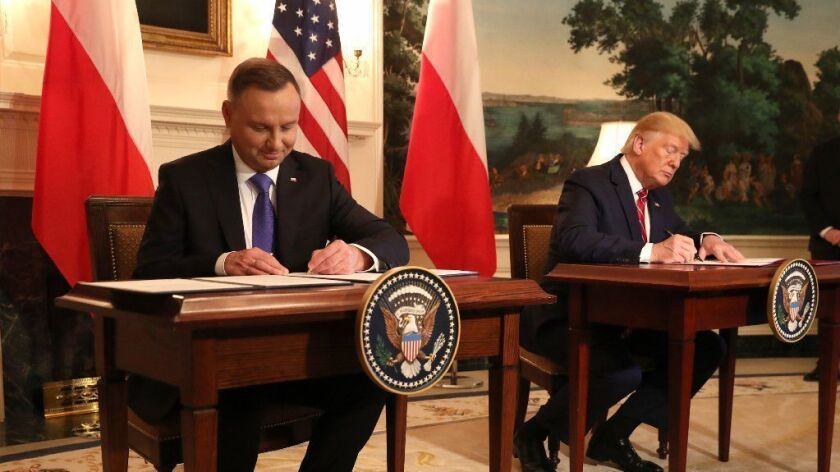 U.S. President Trump and Polish President Andrzej Duda sign a defense deal at the White House on Thursday.