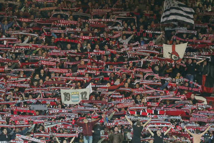 In this photo dated Thursday, Feb. 19, 2015, Guingamp fans hold up scarves during the Europa League soccer match between Guingamp and Dynamo Kiev in the Roudourou stadium in Guingamp, western France. With one of the puniest budgets in France's top division, Guingamp can't splash the cash like some of the mammoths — Qatar-owned Paris Saint-Germain being the prime example — it competes against and humbles from time to time.(AP Photo)