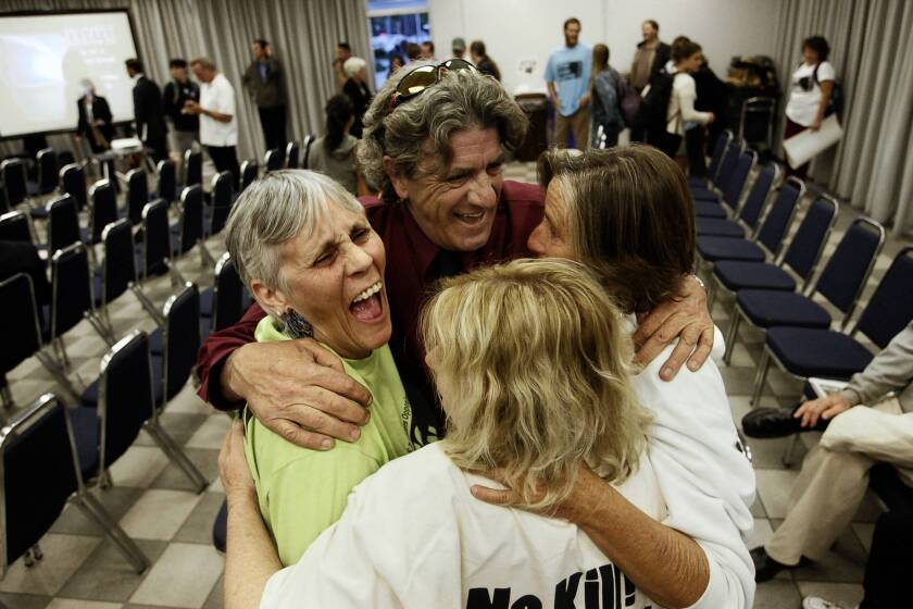 Hunter Kilpatrick, center, of the California Gray Whale Coalition celebrates with Molly Johnson, left, Mandy Davis, right, and Marla Jo Bruton after the California Coastal Commission denied PG&E; a permit for offshore seismic tests.