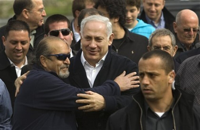 Likud Party leader Benjamin Netanyahu, hugs a supporter during an elections campaign tour in the northern Israeli village of Aniam, Sunday, Feb. 8, 2009. Israel seems to be moving rightward going into Tuesday's national election, with polls giving the edge to former Prime Minister Benjamin Netanyahu and a tough stance on Mideast peacemaking that could lead to a collision with the new U.S. administration. (AP Photo/Sebastian Scheiner)