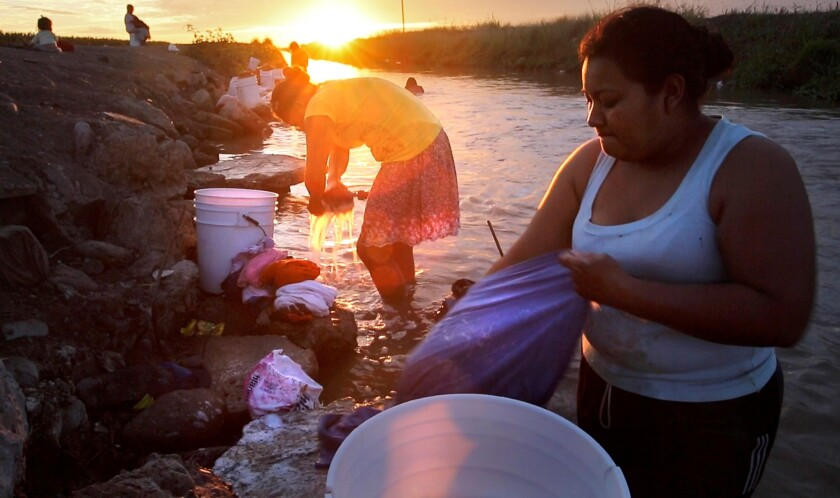 Women scrub their laundry on rubble in an irrigation canal at the Campo Isabelita farm labor camp in Costa Rica in the Mexican state of Sinaloa.