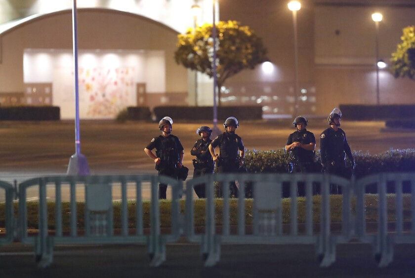 Police stand on the corner of South Coast Plaza at Sunflower Avenue and Bristol Street in Costa Mesa on Monday, guarding against a demonstration over the death of George Floyd.