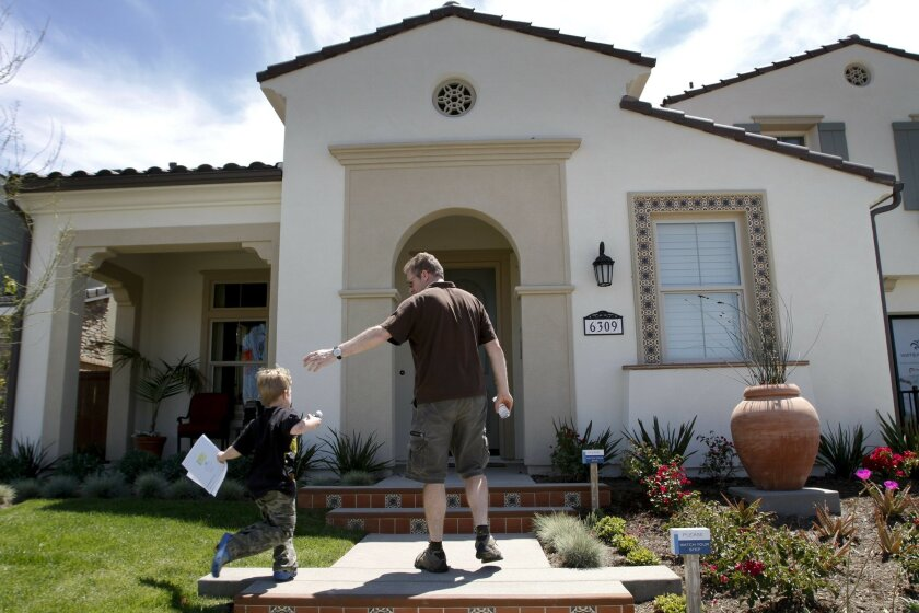 Peter McNamara and his 6-year-old son Rory get ready to enter a model home at a Pardee Homes community, called Watermark, in Carmel Valley on Sunday.