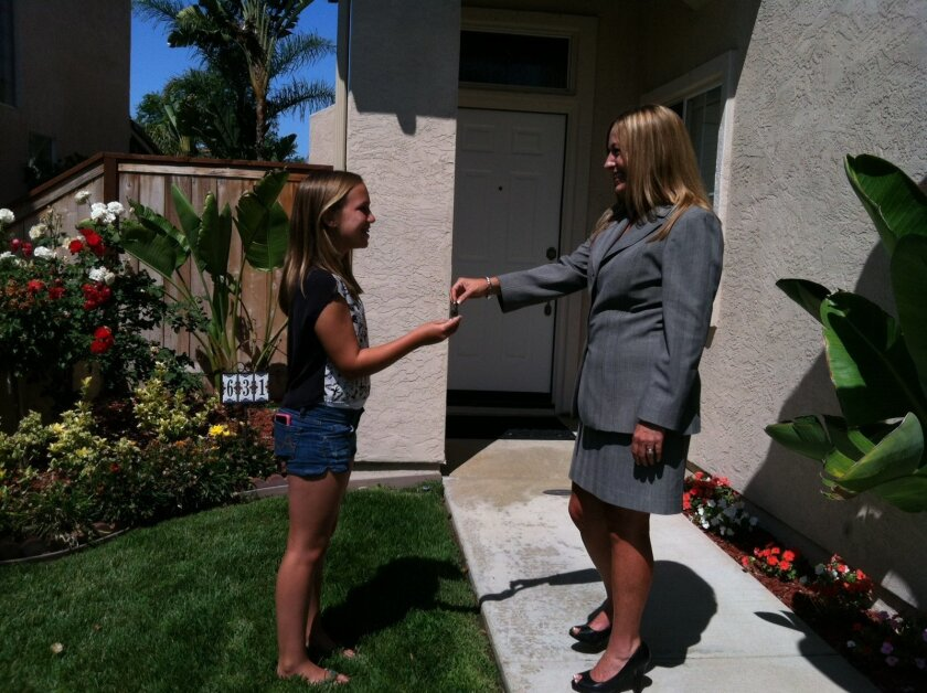 "Real estate agent Catherine ""Cat"" Adair, right, hands the keys to a San Marcos home to 11-year-old Faith McNeilly, whose parents recently closed on the property earlier this month. Faith wrote a letter to the seller that explained why her family should get the house. Courtesy photo."