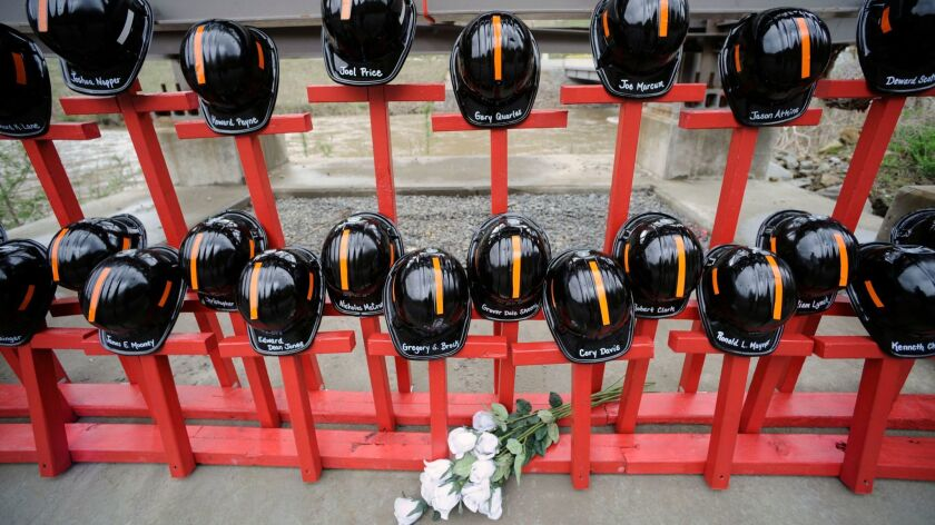 Mine helmets and painted crosses sit at the entrance to Massey Energy's Upper Big Branch coal mine in Montcoal, W.Va., as the memorial representing the 29 coal miners who were killed in an explosion at the mine.