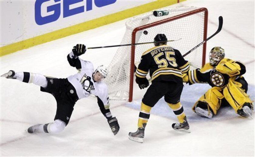 Pittsburgh Penguins defenseman Paul Martin (7) goes flying after scoring against Boston Bruins goalie Marty Turco, right, as defenseman Johnny Boychuk (55) watches during the first period of an NHL hockey game in Boston, Tuesday, April 3, 2012. (AP Photo/Elise Amendola)