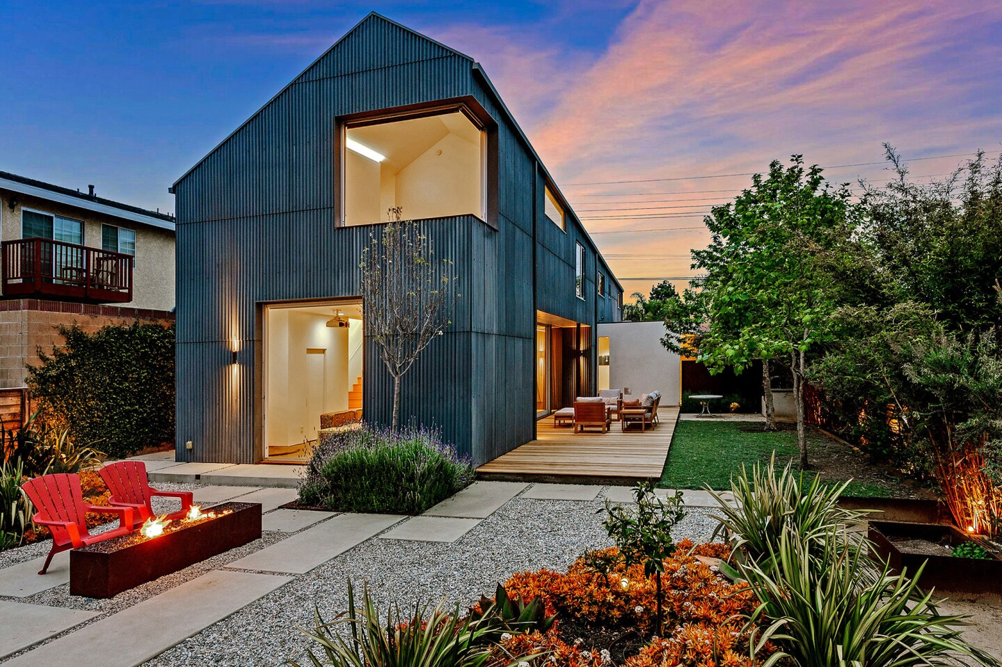 Dark, cement fiberboard-siding provides a visual contrast to the home's white-walled living spaces.