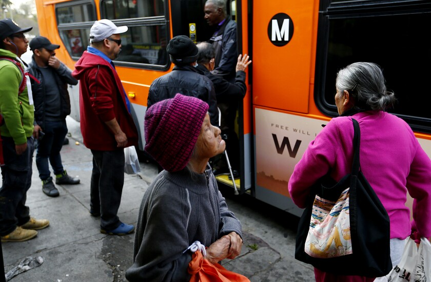 Commuters catch a bus at 7th and Alvarado streets in Westlake