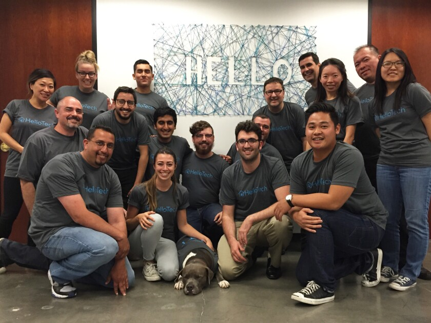 """Richard Wolpert, in back, crouching below the """"o"""" in the """"Hello"""" sign, gathers with other members of the HelloTech team. The Los Angeles start-up charges $79 an hour to have someone come to a home to help with tech issues."""
