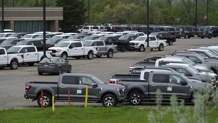 Ford pickup trucks built lacking computer chips are shown in parking lot storage in Dearborn, Mich., Tuesday, May 4, 2021. Automakers are cutting production as they grapple with a global shortage of computer chips, and that's making dealers nervous. (AP Photo/Paul Sancya)
