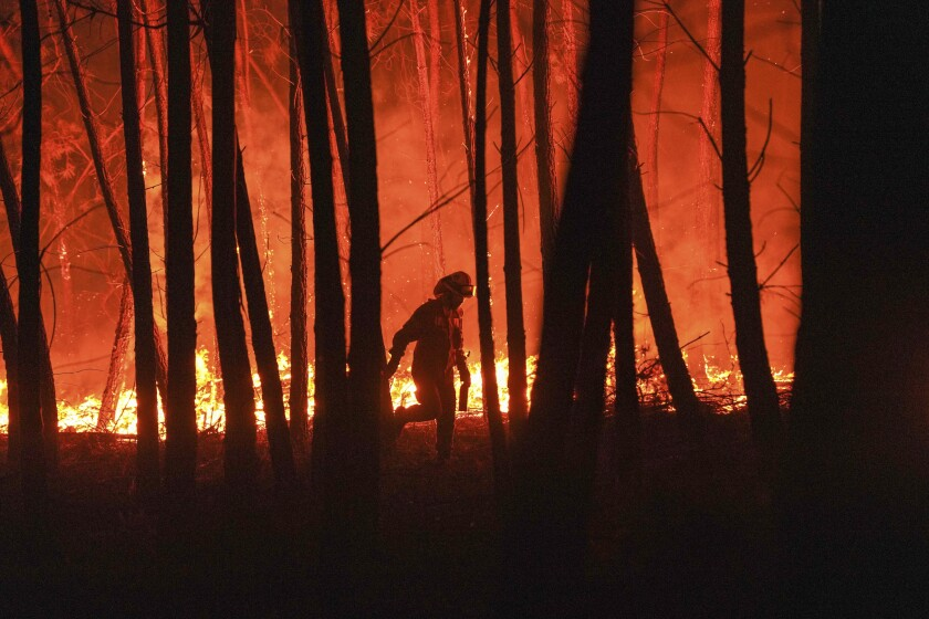 A firefighter is silhouetted against a fire burning outside the village of Roqueiro, near Oleiros, Portugal, Monday, Sept. 14, 2020. Almost 1,000 firefighters are battling a major wildfire in central Portugal. Officials said that strong winds were pushing the flames through dense and hilly woodland, much of it hard to reach. (AP Photo/Sergio Azenha)