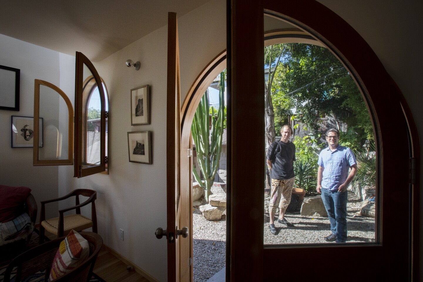Two men stand outside a writing studio looking in, framed by an arched doorway.