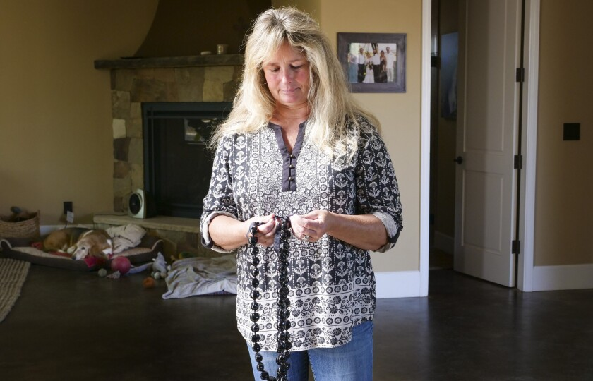"""In this Monday, Nov. 4, 2019, photo, Tina Chandler looks through her Kukui Nut Lei, as she recalls packing them with a family portrait when she evacuated with during the Kincade Fire, in the Fountaingrove neighborhood of Santa Rosa, Calif. Two years ago, the Chandlers had only minutes to escape before their longtime family home burned to the ground before their eyes. They rose from the ashes to build a new home. The night of the fire Chandler packed a framed family photo along with a box of kukui nut necklaces that a friend had sent from Hawaii after they lost their home. """"I know that sounds kind of silly,"""" she said of the black shiny nuts, which represent hope and renewal. """"But this was their way of saying 'We're going to be alright."""" (AP Photo/Lacy Atkins)"""