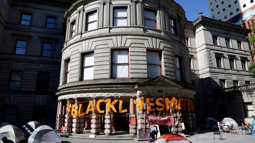 """Large letters spell out """"Black Lives Matter"""" on the portico at Portland City Hall after the building was shut down in response to a protest."""
