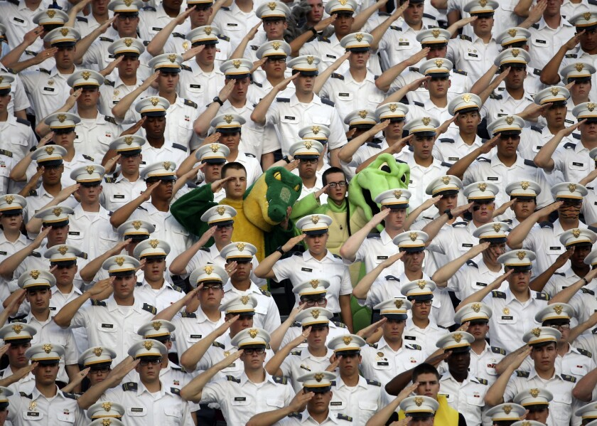 Cadets salute during the national anthem before a football game between Army and Fordham in West Point, N.Y.