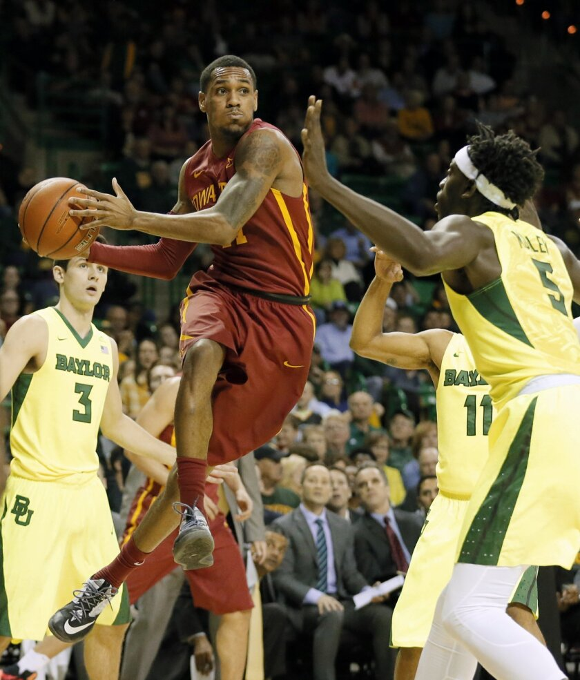 Iowa State's Monte Morris (11) is forced to pass the ball out from beneath the basket as Baylor's Jake Lindsey (3), Johnathan Motley (5) and Lester Medford (11) defend in the first half of an NCAA college basketball game, Tuesday, Feb. 16, 2016, in Waco, Texas. (AP Photo/Tony Gutierrez)