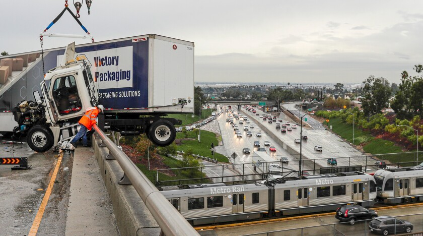 A big rig dangles over a ramp connecting the 710 and 60 freeways in Los Angeles amid steady rain early Wednesday. Heavy precipitation is expected to continue through the morning rush hour.