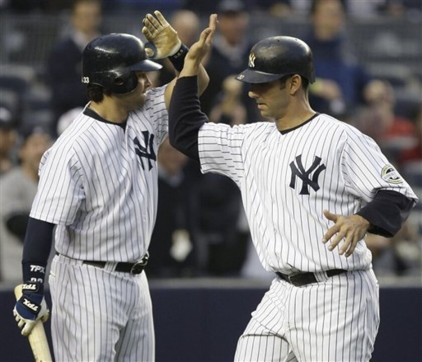 New York Yankees' Nick Swisher, left, greets Jorge Posada at home plate after Posada hit a two-run home run against the Los Angeles Angels in the first inning during a baseball game Friday, May 1, 2009 at Yankee Stadium in New York. (AP Photo/Julie Jacobson)