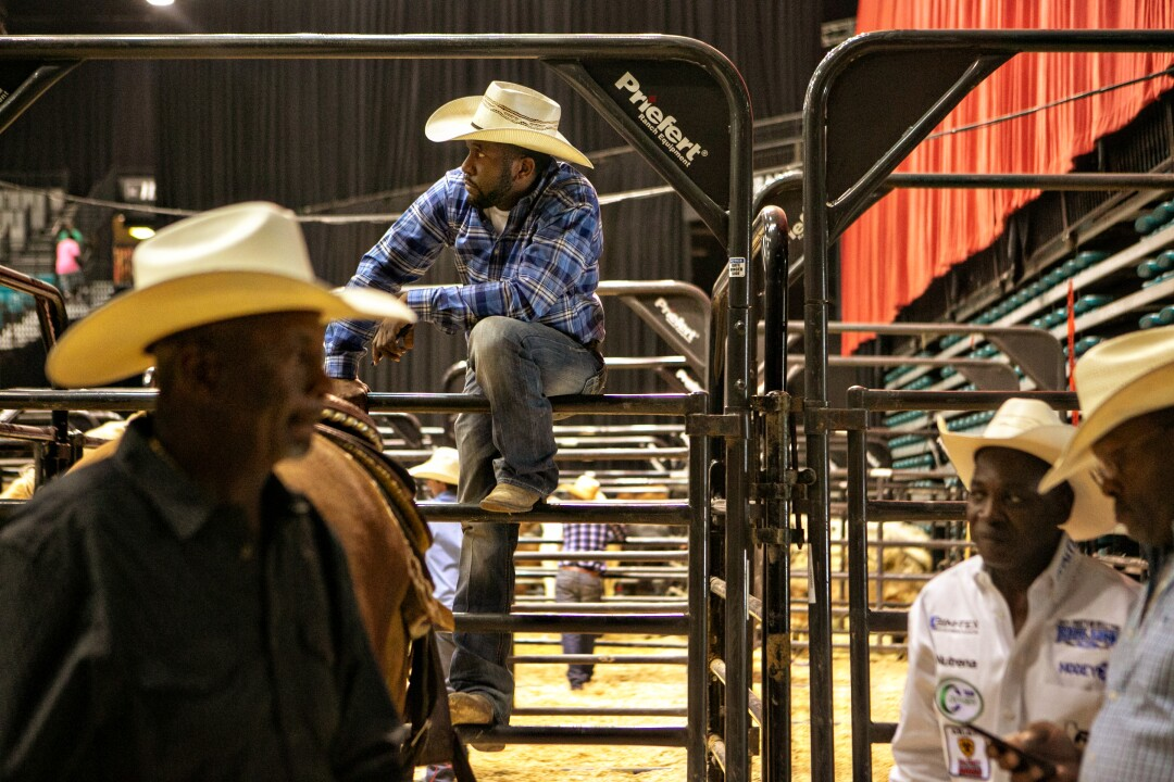 Cowboys gather around the stock holding pens at the Bill Pickett Invitational Rodeo.