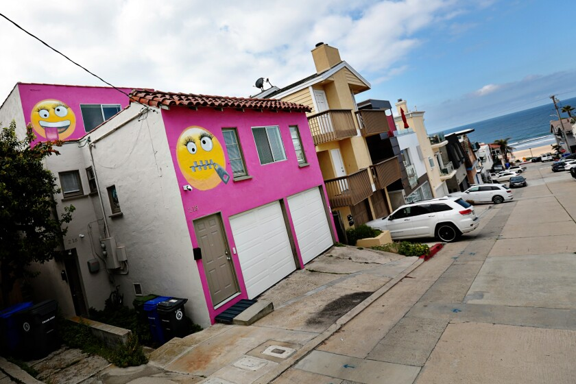 The hot-pink house adorned with two giant emojis that roiled a Manhattan Beach neighborhood has sold  for $1.55 million.