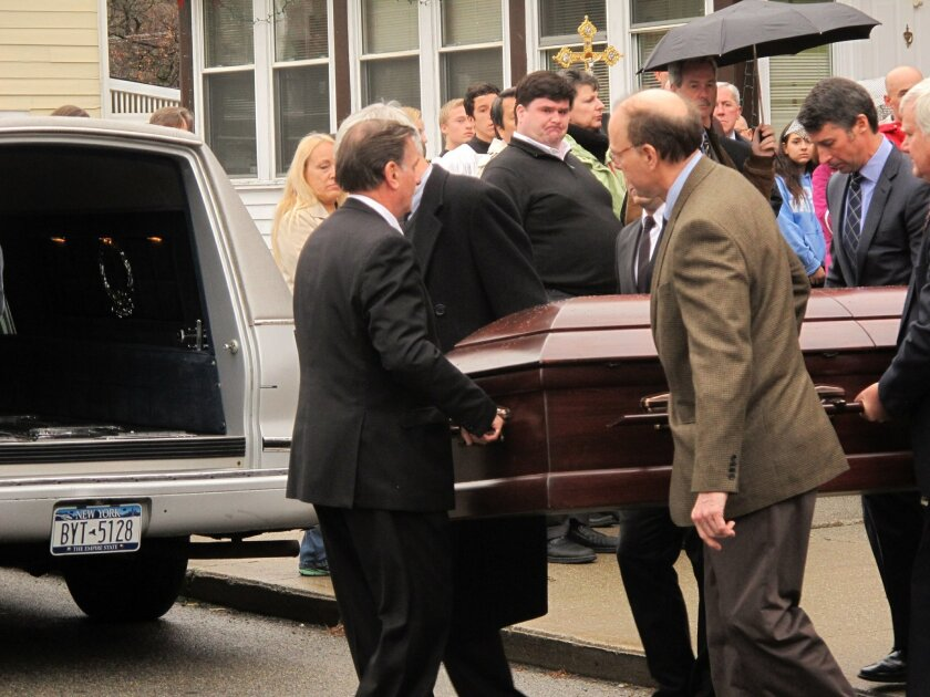Pallbearers carry the casket to a waiting hearse after the funeral of Jim Lovell in Cold Spring, N.Y., on Dec. 6, 2013. Lovell and three others died when the Metro North commuter train he was riding in derailed and tumbled off the tracks on Sunday, morning, Dec. 1. Sixty others were injured in the accident.(AP Photo/Jim Fitzgerald)